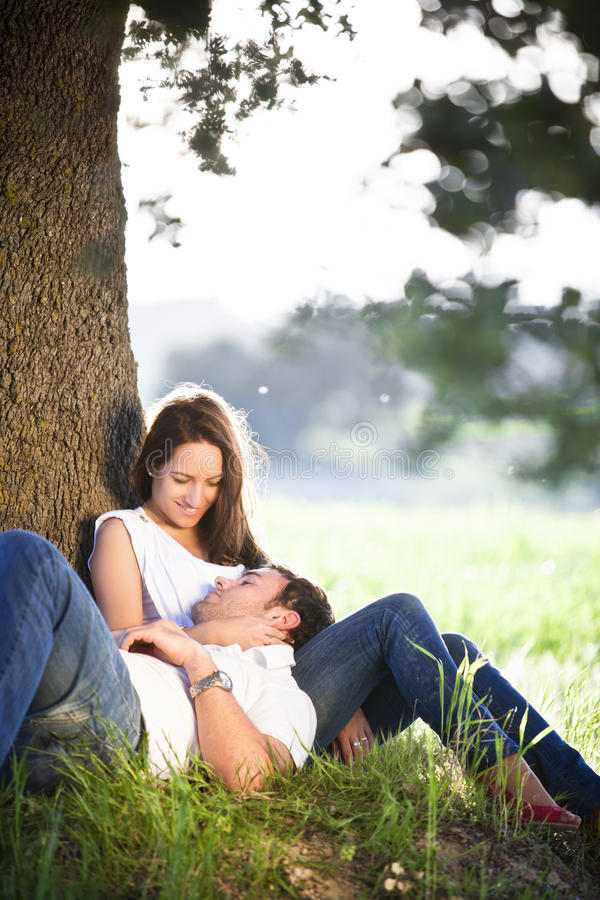 Resting young couple. Young beautiful couple resting under a tree