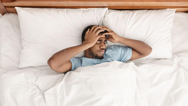 Restless african american man waking up with headache royalty free stock image