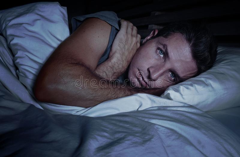 Restless worried young attractive man awake at night lying on bed sleepless with eyes wide opened suffering insomnia sleeping diso stock images