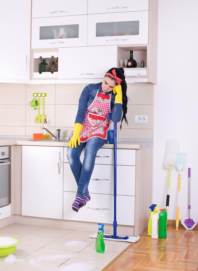 Restng da senhora de limpeza na bancada da cozinha imagens de stock