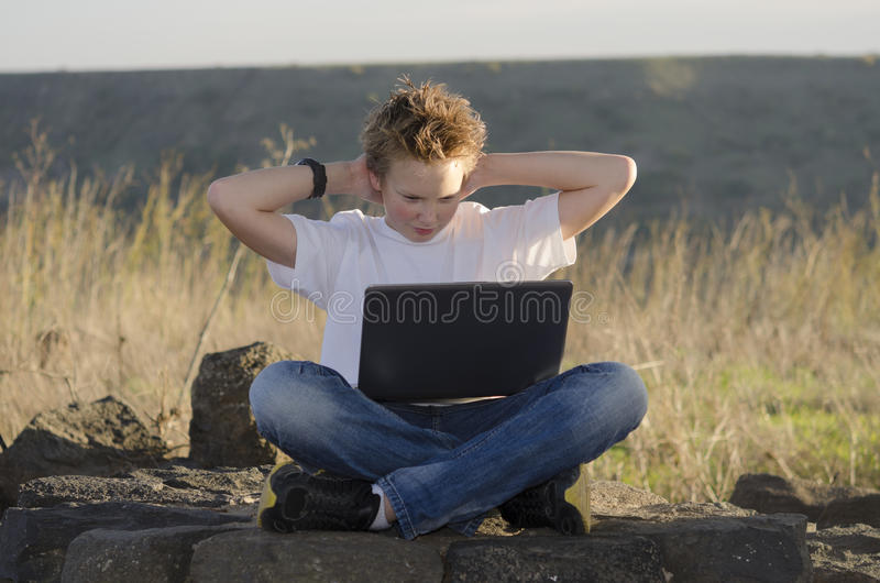 Resto adolescente com mãos da posse do portátil atrás de sua cabeça fotografia de stock royalty free