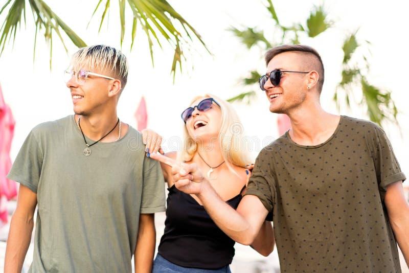 Resto alegre da empresa de três amigos em uma praia e em um drin tropicais imagem de stock