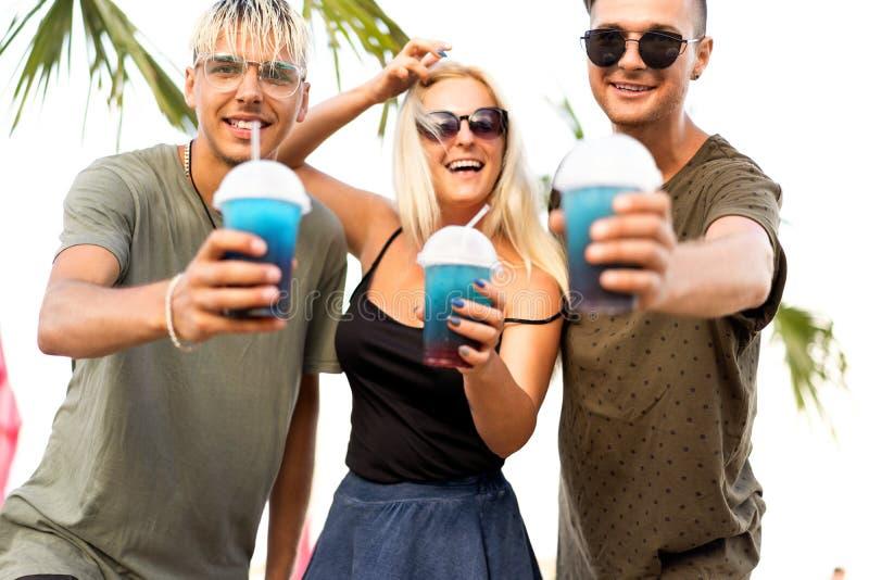 Resto alegre da empresa de três amigos em uma praia e em um drin tropicais imagem de stock royalty free