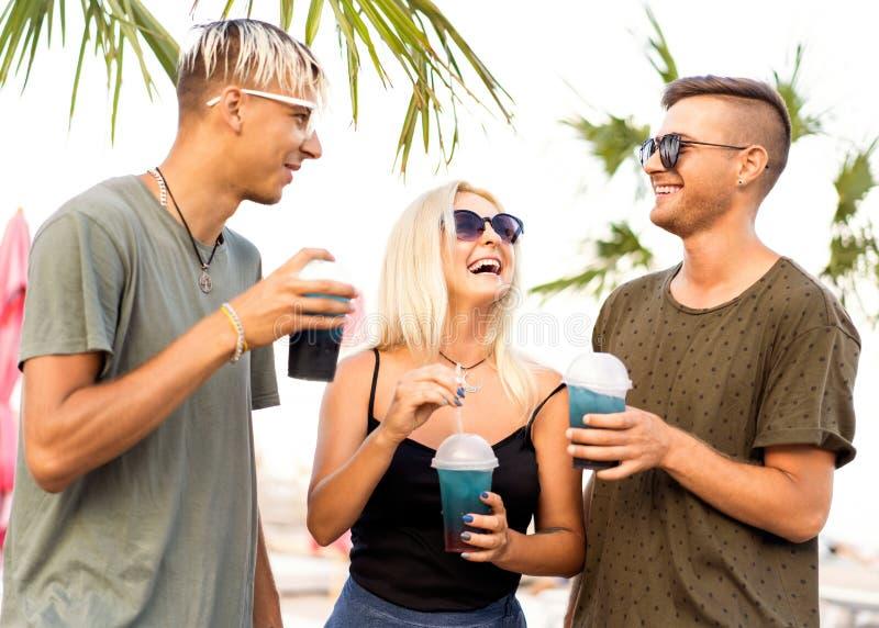 Resto alegre da empresa de três amigos em uma praia e em um drin tropicais fotos de stock royalty free