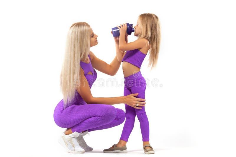 Resto da mamã e da filha após a aptidão com um abanador nas mãos Isolado no fundo branco fotos de stock royalty free