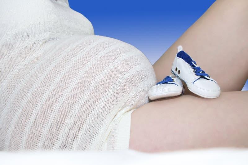 Resto de los botines del bebé azul contra la panza del lleno-término imagen de archivo