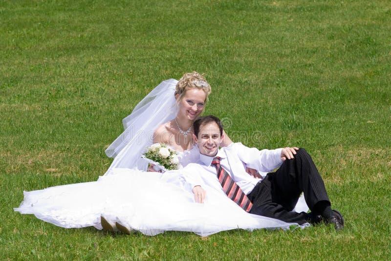 Resto de los pares nuevo-casados en la hierba fotografía de archivo libre de regalías