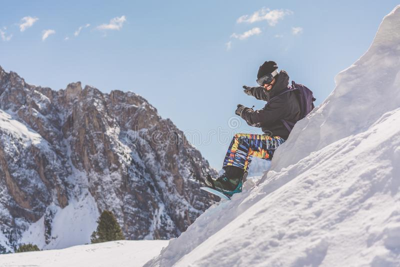 Resto de tomada snowboarded de sorriso farpado após a sessão do passeio Homem novo que refrigera sobre a montanha da neve borrado fotografia de stock