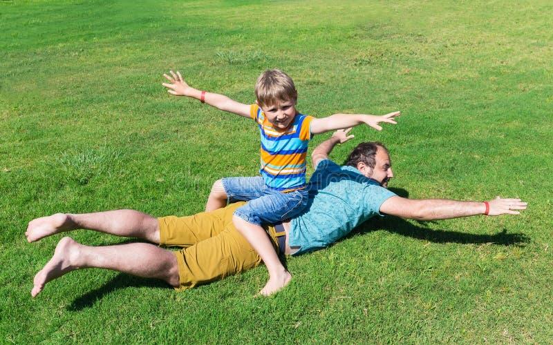 Resto del pap? y del hijo en hierba en d?a de verano soleado imagen de archivo