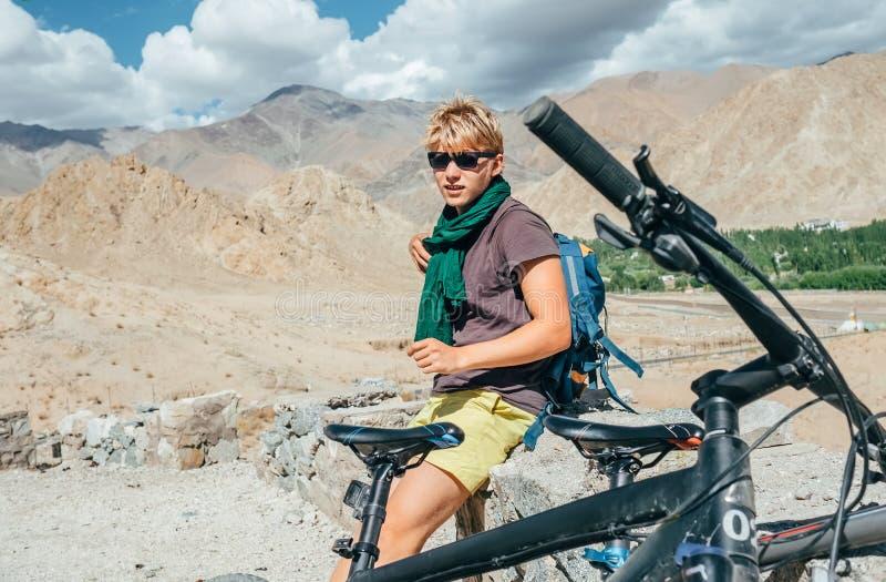 Resto del viajero de la bici del hombre joven en el camino de la alta montaña en Himalaya imagen de archivo