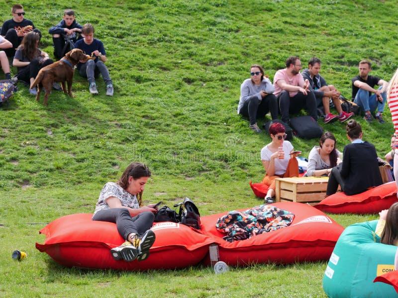 Resto della gente sui materassi gonfiabili rossi disposti sull'erba verde fotografia stock libera da diritti