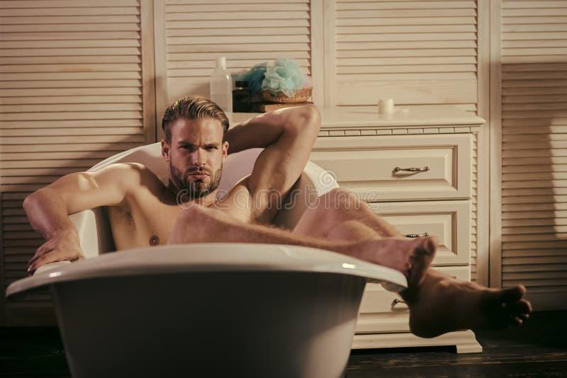 Resto después del trabajo El machista relaja desnudo en bañera en cuarto de baño fotos de archivo