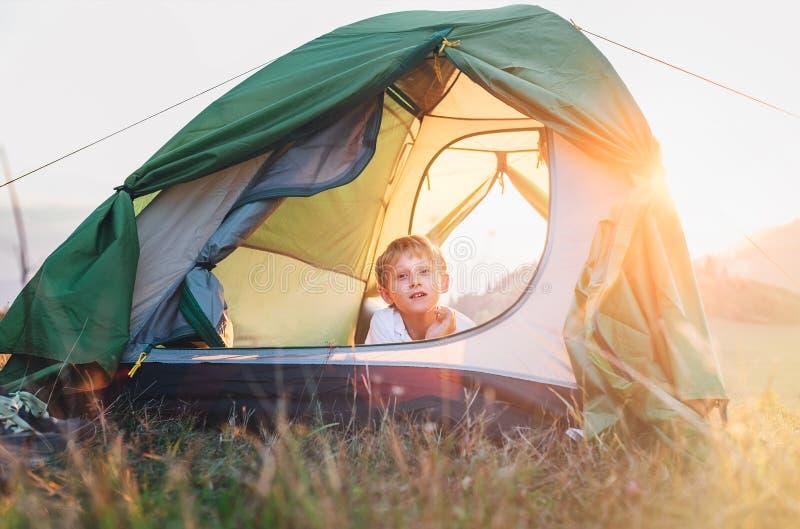 Resto do menino na barraca de acampamento Tempo do por do sol na natureza imagens de stock