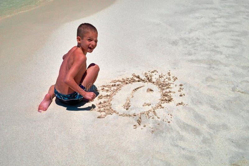 Resto do verão do conceito pelo mar O menino de riso olha a câmera que senta-se na areia na linha da ressaca A criança bonito pin foto de stock