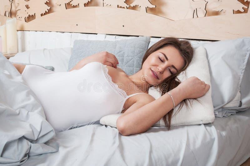 Resto, dormire, comodità e concetto della gente - giovane donna che allunga a letto a casa camera da letto immagine stock