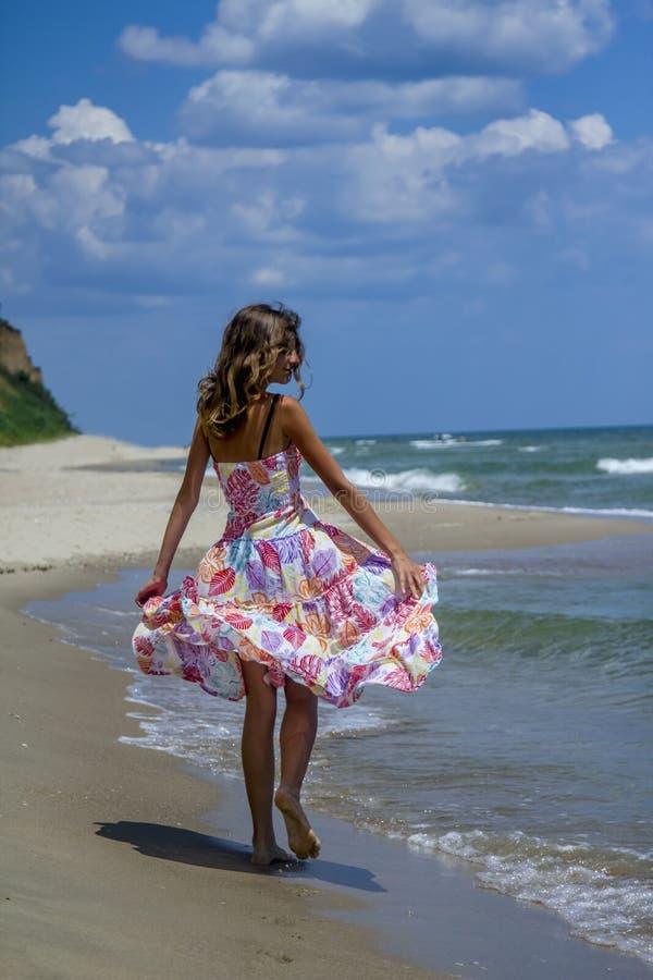Resto moreno novo bonito feliz da menina na praia contra o SE imagem de stock royalty free