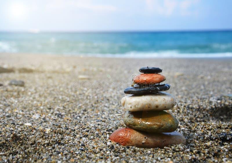 Resto nel concetto di estate Pietre accatastate sulla spiaggia contro il mare, spazio della copia, luce solare fotografia stock