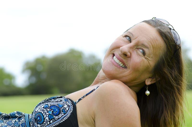 Resto relaxed de la mujer madura hermosa en parque foto de archivo