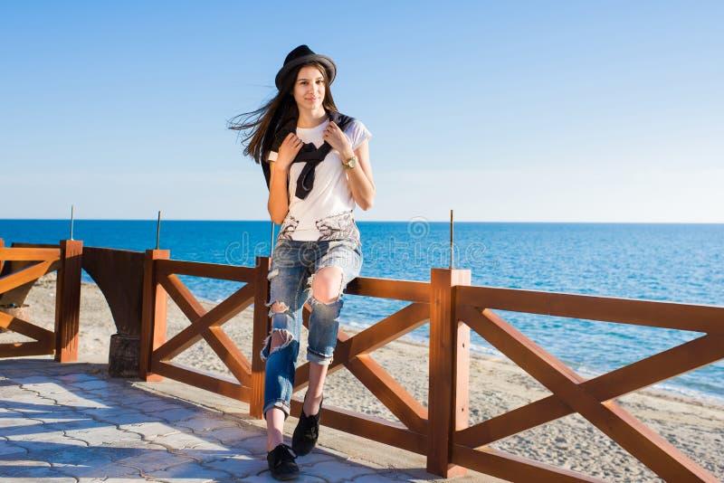 Resto splendido della ragazza dei pantaloni a vita bassa all'aperto mentre passeggiando lungo la spiaggia nella stagione primaver immagini stock