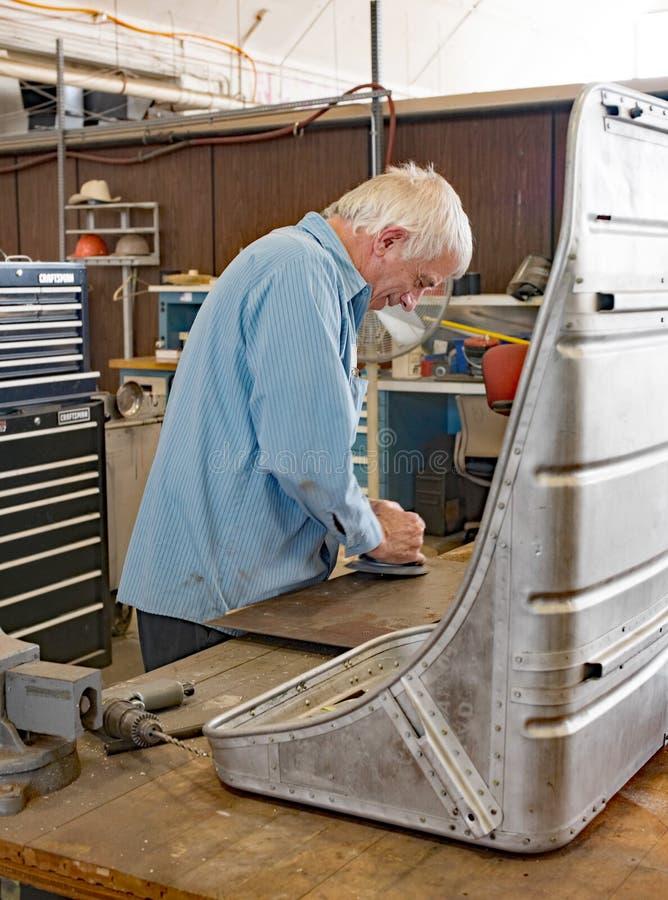 Restoration Worker Buffing Aluminum for Memphis Belle Co-pilot Seat. Dayton, Ohio, USA - November 18, 2016: Restoration worker at the National Museum USAF is stock photo