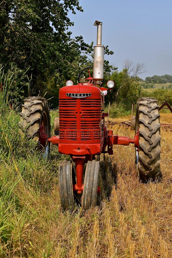 Restored M Farmall tractor in a field. ROLLAG, MINNESOTA, Sept 2, 2017: A restored M Farmall tractor is parked and ready for live field demonstrations at the stock images
