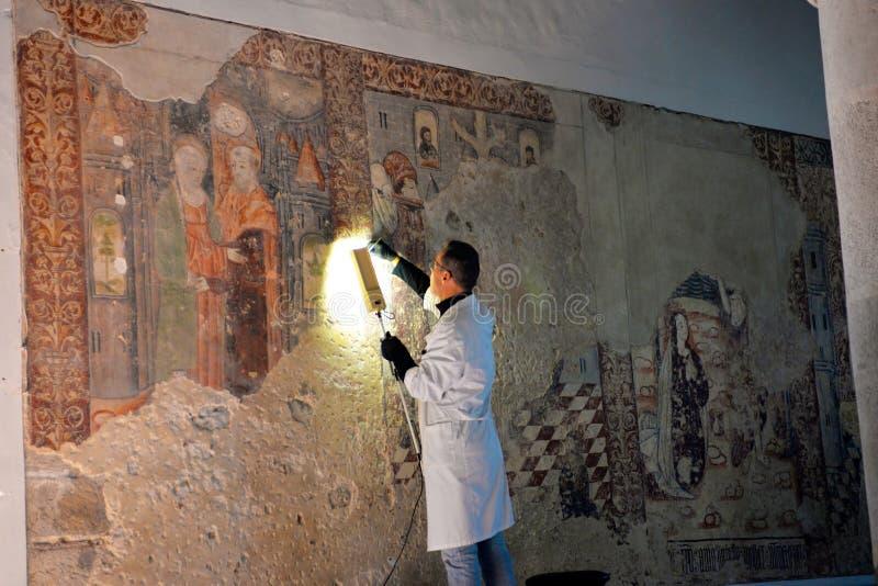 Restoring Artisan Repairing Medieval Wall Frescoes, Craft, Religion and Art. Restoring artisan, with his back to lens, repairing some medieval wall frescoes that royalty free stock image