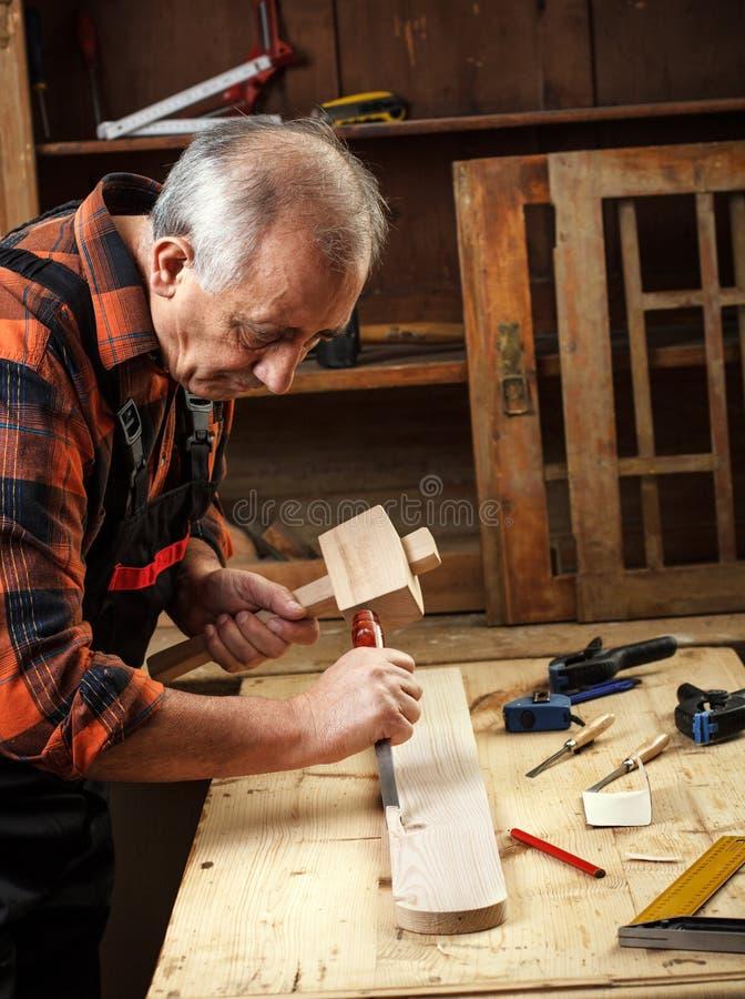 Restoring old furniture. Senior carpenter restoring old furniture royalty free stock photography