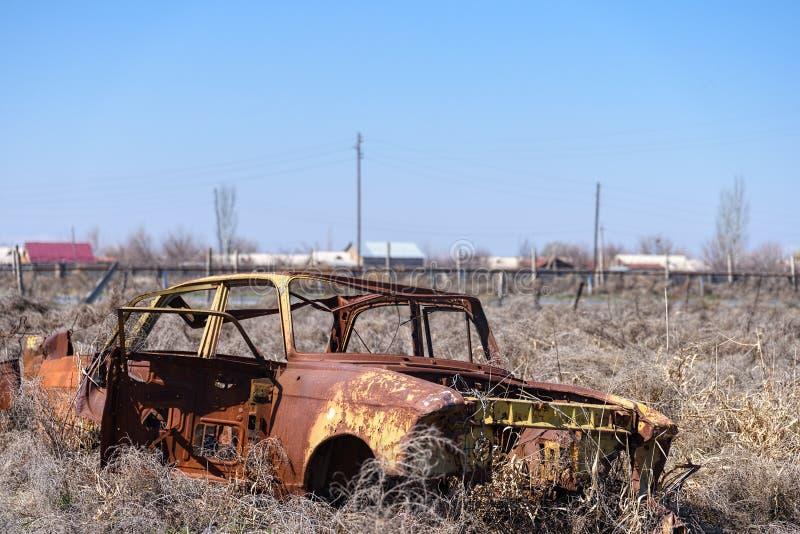 Restos abandonados de un coche ruso soviético amarillo en el medio del heno seco en Armenia meridional imagenes de archivo