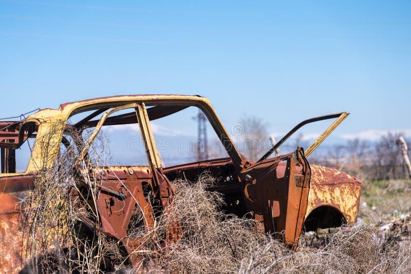 Restos abandonados de un coche ruso soviético amarillo en el medio del heno seco en Armenia meridional imágenes de archivo libres de regalías
