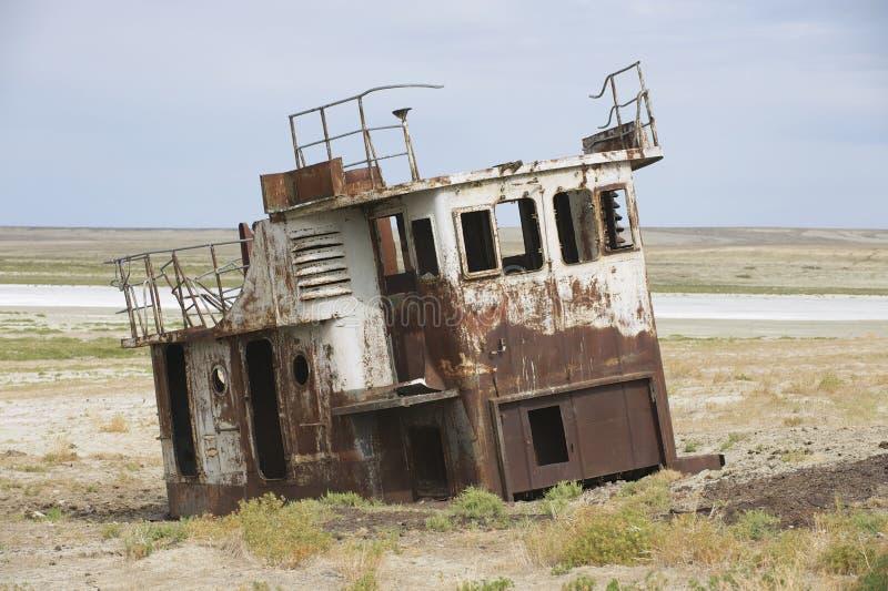 Restos aherrumbrados de los barcos de pesca en la cama de mar del mar de Aral, Aralsk, Kazajistán foto de archivo
