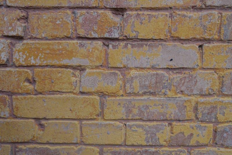 Restos de la pintura amarilla en la pared de ladrillo imagen de archivo libre de regalías