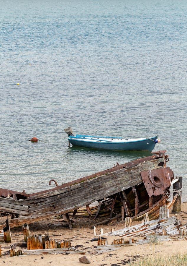 Restos de una nave abandonada destruida en la orilla, un símbolo de la decadencia y de la degradación, y barco de motor moderno foto de archivo libre de regalías
