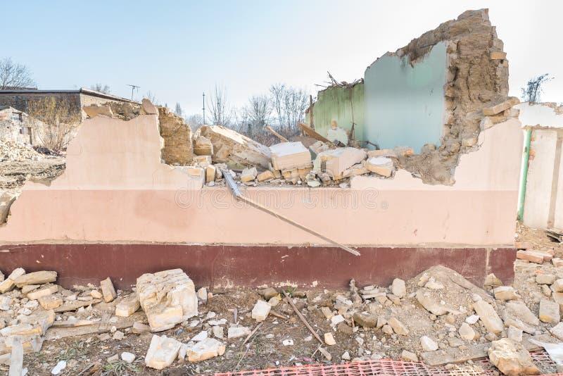 Restos del daño del desastre de las consecuencias del huracán o del terremoto en casas viejas arruinadas con el tejado y la pared foto de archivo libre de regalías