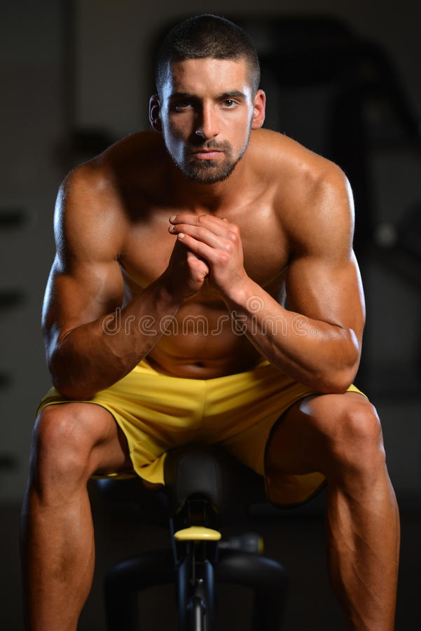 Restos del hombre en el gimnasio después que tiene un entrenamiento foto de archivo libre de regalías