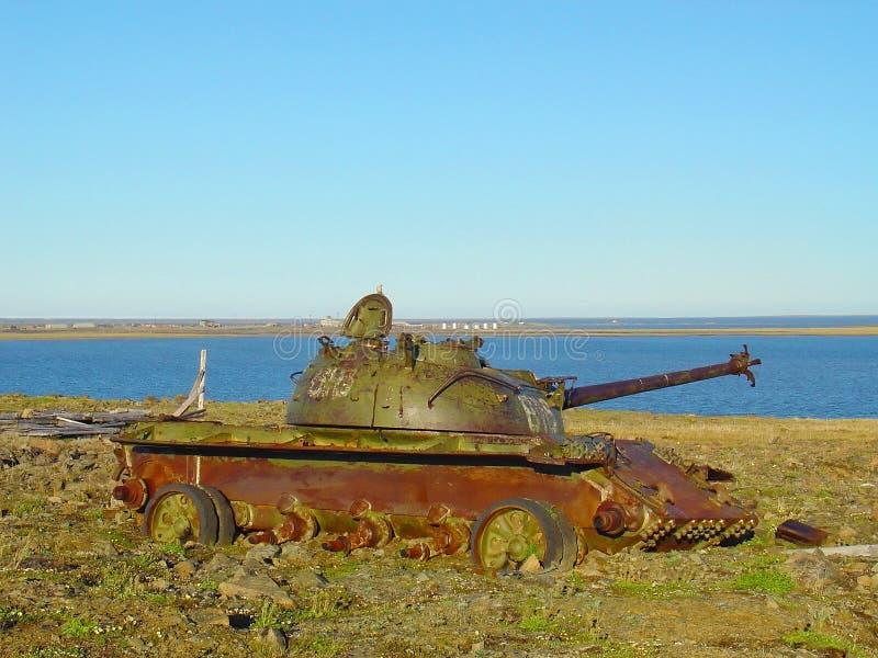 Restos do tanque de guerra soviético antigo que corrói-se fora no depósito da sucata no fundo natural cênico da paisagem Símbolo  fotografia de stock