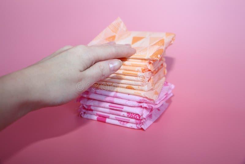 Restos fêmeas bonitos de uma mão em diversas almofadas sanitárias fotos de stock