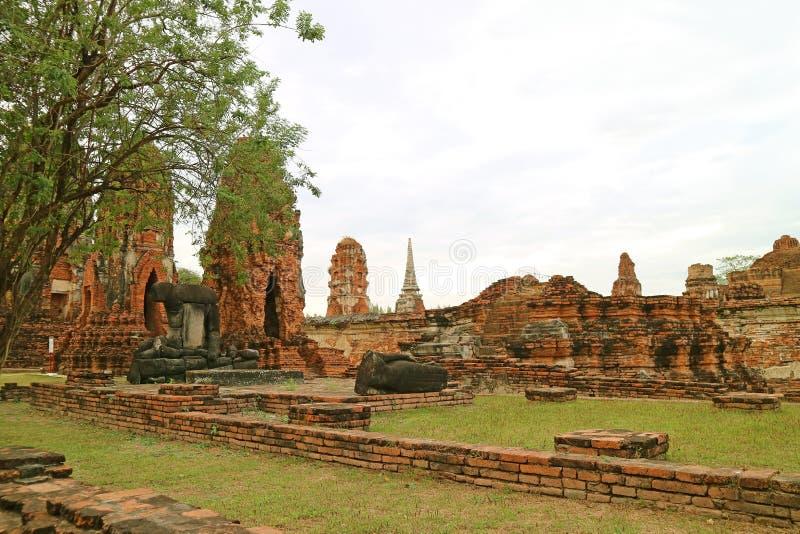 Restos increíbles de las imágenes de Buda que se sientan y de descansos en Wat Mahathat Temple, parque histórico de Ayutthaya, Ta fotos de archivo