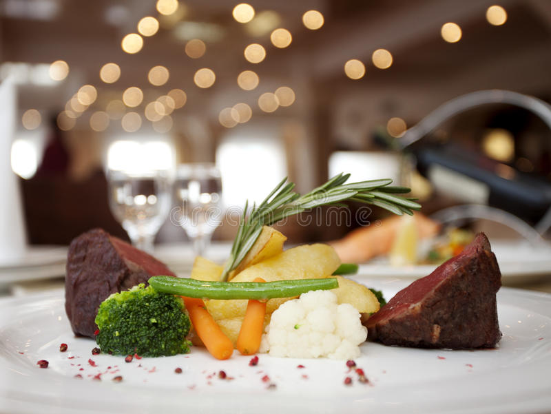 Restaurant dinner. Dinner with beef meat, vegetables and wine in a restaurant royalty free stock image