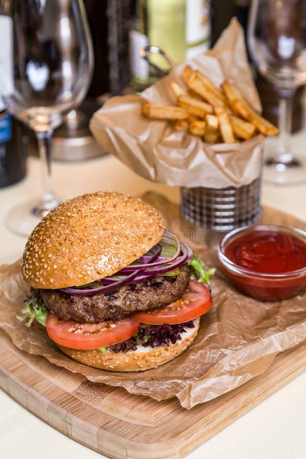 Restourant-Servierteller - Burger mit Kotelett mit dem Braten der Kartoffel stockbilder