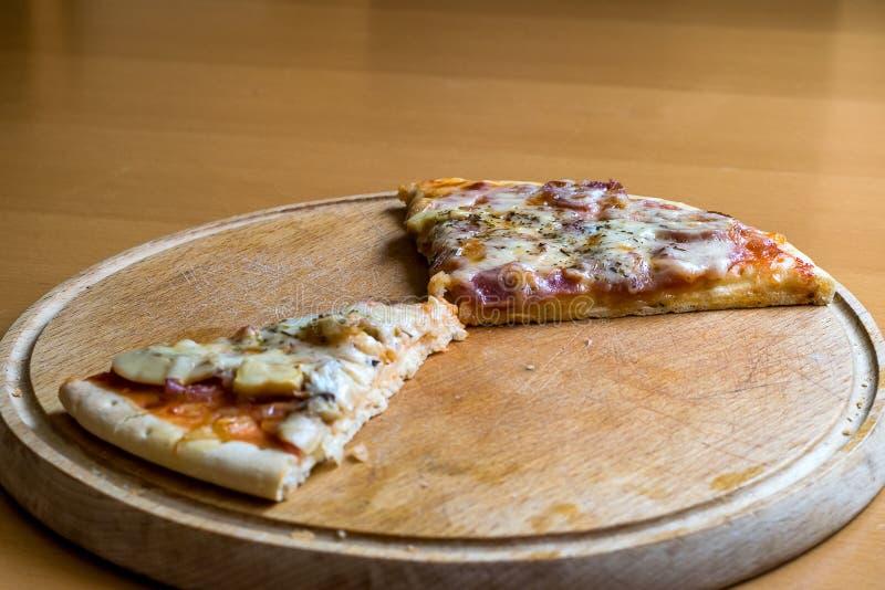 Restra pizzastycken på en träskärbräda arkivbilder