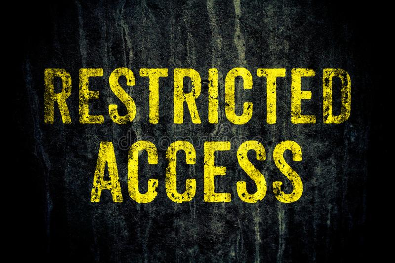 Restricted access warning danger sign in yellow letters painted over dark grungy cement concrete wall. stock photos