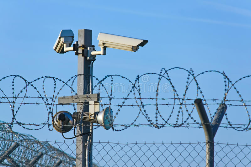 Restricted area. CCTV cameras, lights and fence stock photography