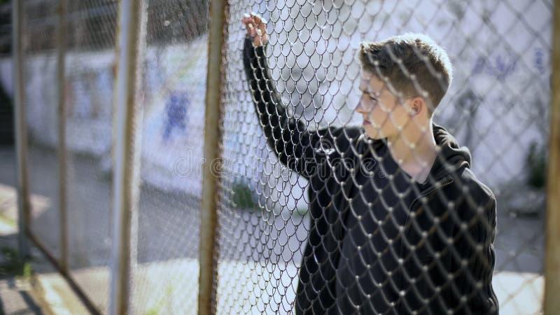Restrictions d'internat, garçon de l'adolescence derrière l'emprisonnement de barrière, avenir cassé images stock