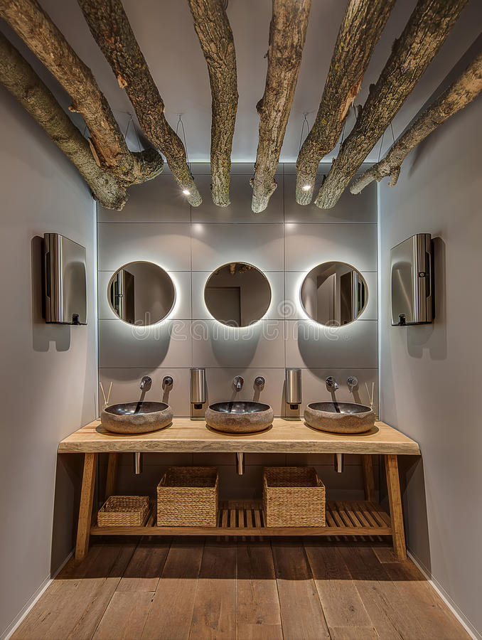 Restroom in modern restaurant. Washroom a modern style with gray wall and a parquet the cafe. There are hanging logs with lamps, mirrors with backlight, wooden stock photo