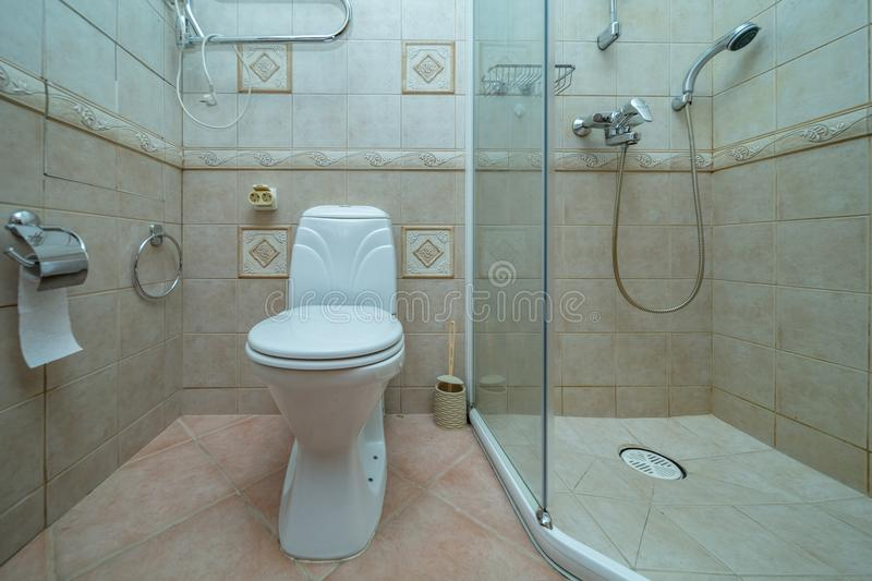 Restroom with toilet. Toilet bowl in small bathroom with shower Room with brown tile decoration stock image