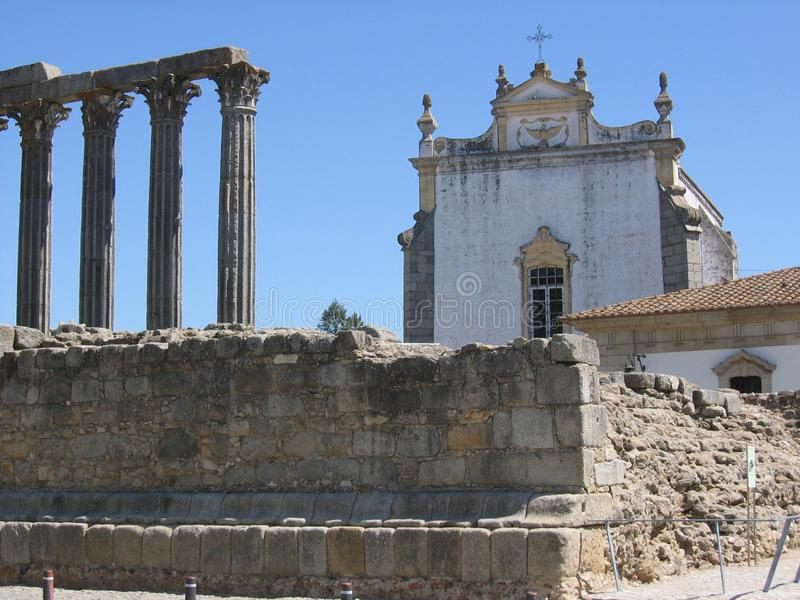 Rests of an old temple in front of a Gothic church , St John Evangelist. Evora. Portugal stock photos