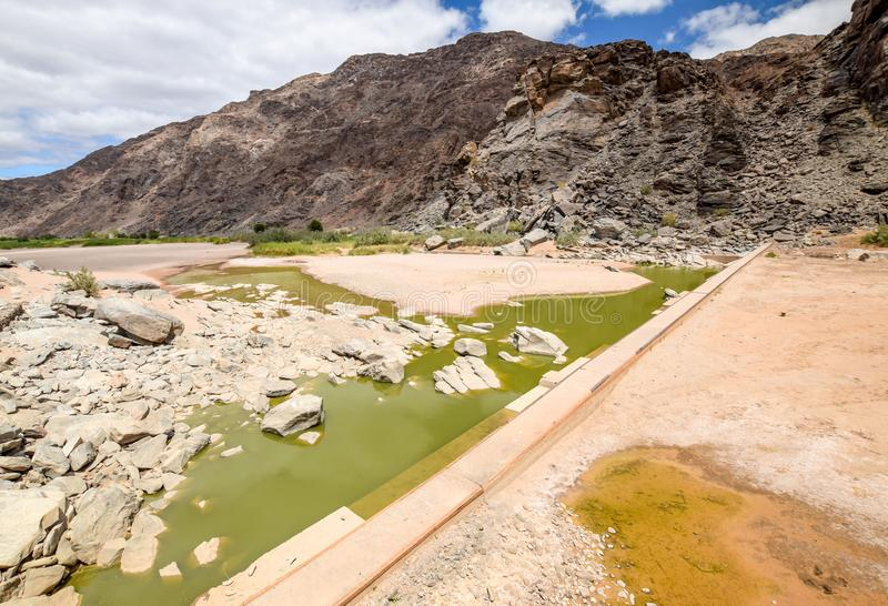 Rests of water and an old dam during dry season near Ai-Ais Hot Springs at Fish River Canyon, Namibia. Rests of water and an old dam during dry season near Ai stock image