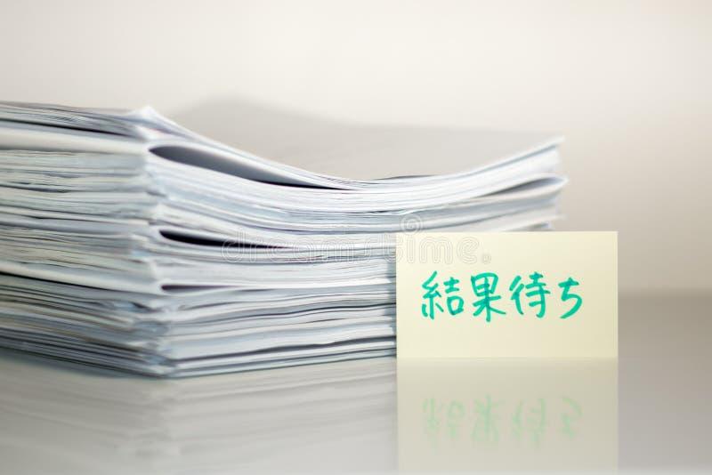 Resultado que espera; Pila de documentos en el escritorio y el fondo blancos imágenes de archivo libres de regalías