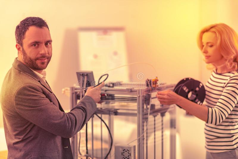 Diligent responsible coworkers focused on the process of building the 3D printer. royalty free stock images