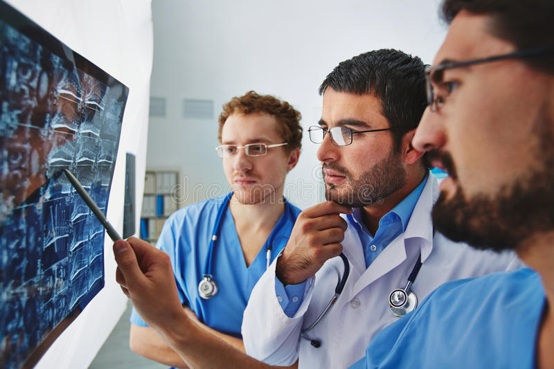 Results of x-ray. Young male doctors looking attentively at x-ray and discussing it royalty free stock image